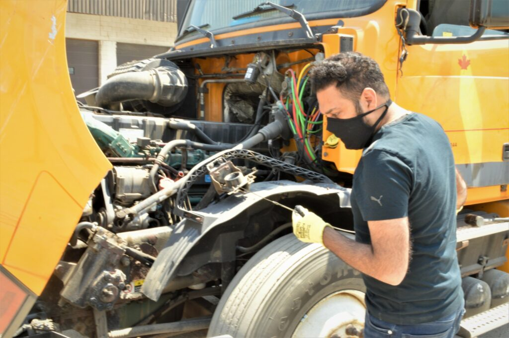 A driver checks the engine oil level before setting out on a trip. (Photo: Leo Barros)