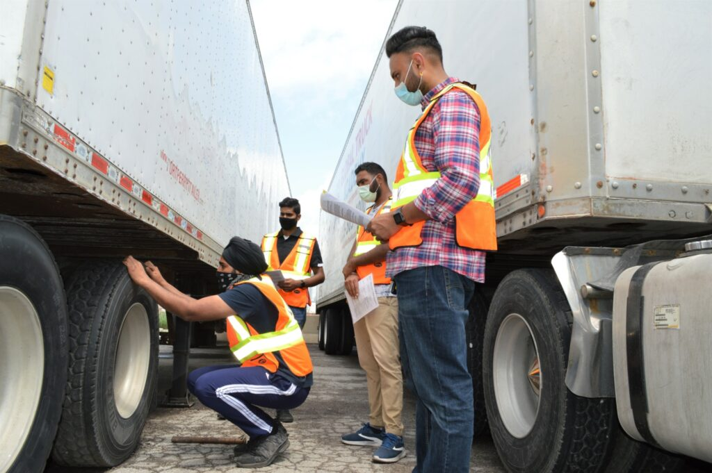 Students inspect tires on a trailer at Global Truck Academy in Brampton, Ont. Proper pre-trip inspections keep everyone safe on the road. (Photo: Leo Barros)